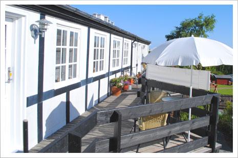 På altangangen er der en lille hyggekrog med havemøbler og parasol.